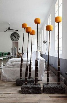BLACK 94 by Paola Navone for Gervasoni Coat stand in black bamboo, Borobudur stone base, orange cotton pompons. Paola Navone's Apartment in Paris.