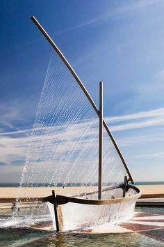"""Fuente a la actividad marinera -  Paseo maritimo de la Malvarrosa........  Escultura que representa a una barca con la vela desplegada. Construida en aluminio, mármol y granito. Un juego de cortinas de agua completan el diseño. Colocada en el año 1999, fue diseñada por el Servicio del ciclo integral del agua. La barca parece flotar sobre un circular lago. Tamibén se le conoce como """"Font de la Nau de L'aigua""""."""