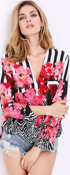 Take center stage in this bold and unique floral design blouse. Our V-neckline blouse is a sexy statement piece and goes great with a black pencil skirt for the perfect day- time office look.