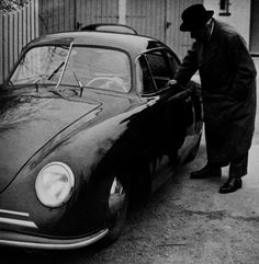 "1950. Ferdinand Porsche standing next to the 356 ""Gmünd Coupé"" with his son Ferry Porsche at the wheel. Behind the car is the double garage of Porsche's villa in Stuttgart, in which the first Volkswagen prototypes were built"