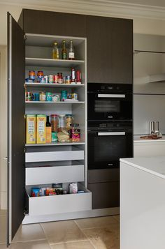 The tall storage cabinet, adjacent to the hob, is home to cooking ingredients and everyday items, all at easy reach for the homeowners.