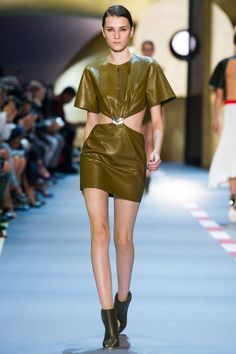 Olive drab and army green were transformed into body-con minidresses and separates. Cut-outs at the waist, shoulder (or both) were balanced by either looser or longer shapes.    - HarpersBAZAAR.com