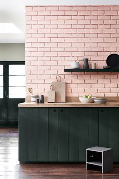 pink brick feature wall and black kitchen cabinets