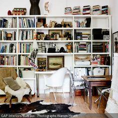 In diesem Wohnzimmer dient der weiß-braune Kuhfellteppich als Eyecatcher. Das großzügige Wandregal bietet viel Platz für Bücher und Dekoelemente. In einer kleinen …