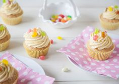 Pale yellow vegan cupcakes with icing and jelly bean toppings, sitting on a white wooden kitchen worktop