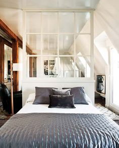 Bedroom divided into sitting area and sleeping area with windows.