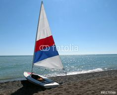A small sailboat, pulled up onto the beach on a warm summer afternoon.