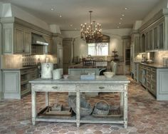 Weathered gray cabinetry works beautifully with the flooring in this kitchen. And the double chandeliers? Perfect!