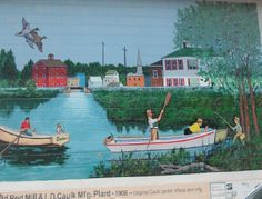 Mural depicting skiffs on the water in fornt of a downtown scene go to http://americanroads.net/art_trails_winter2014.htm for the rest of the story