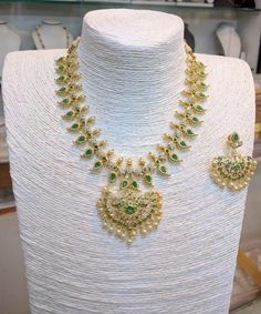 Short mango necklace design with green stones. For more such beautiful jewellery designs, visit our complete catalogue!