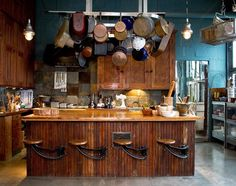 All those pans are kinda distracting, but i love the rustic wood paired with the blue wall color. And i've never seen stools attached to an island like that before!