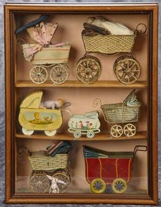 Collection of small tin doll carriages in various styles, in glass-fronted presentation shelf Tiny Dolls, Old Dolls, Victorian Dolls, Vintage Dolls, Miniature Furniture, Doll Furniture, Les Enfants Sages, Antique Dollhouse, Dolls Prams