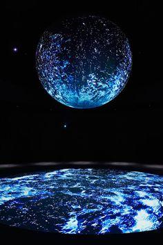 """""""WATER""""はWONDER MOMENTSのはじまりのシーンであり、生命の根源である「水」のふるまいの美しさをテーマとした「水の彫刻」。リアルにダイナミクスシミュレーションされたCGの水が、球体をひとつの大きな容器としてダイナミックに展開するアートインスタレーション。"""