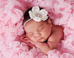 newborn sleeping w/ hands under face in a fluffy tutu