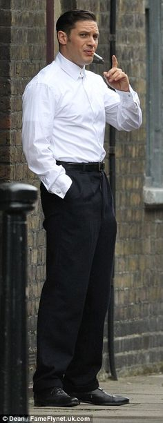 Smoking hot: Tom Hardy wore a white shirt and classic suit trousers as he puffed on a fake cigarette during filming