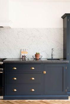 Belgian Blue Fossil worktops and a huge Carrara marble splashback make this Shaker kitchen