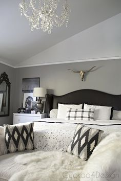 blue, black and white bedroom with leather studded wingback bed