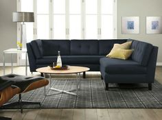 Navy blue sectional and gray walls