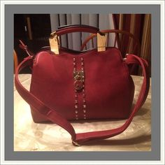 "Maroon handbag. 3rd photo accurate color Maroon colored handbag. Mint condition. Only used it a few times. 3rd pic depicts true color. Maroon colored purse. Gold hardware. Detachable strap.  Vegan leather. Height 8"", width approximately 5"", 1 outside zippered pocket on the back of the purse. Inside features one large zippered center pocket with 2 inside side pockets and another large inside zippered pocket. Alyce Paris Bags"