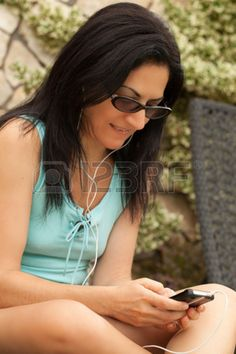 Young Caucasian brunette woman sitting on sunbed outside in the garden and sending messages from smartphone. Stock Photo