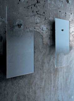 "Fiction Mirrors.  This series of ""fiction"" mirrors designed by Jean-Marie Massaud are made in extralight glass with degrading shaded silvering. They hang on the wall with a chromium-plated metal cylinder. The small mirror can have a degrading shade upwards or downwards."