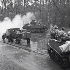 British troops capture Hengelo, the Netherlands! 3rd April 1945. A Sherman turn in front of a Willis Jeep pulling a utility trailer. Also stopped behind the jeep is a British troop carrier....
