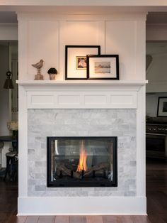This freestanding fireplace boasts a marble, subway tile surround for a formal, elegant look. This contemporary, double sided fireplace fills the space with a lovely, warm glow.