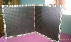 PegBoard Displays Pic 2   1st I used duct tape & went around 3 of the sides to decorate, then I used ribbon & weaved from one hole to the other on the other board, & wala the finished product! You can also add ribbon to the top to make a handle and to the sides to close it when you have your jewelry on it to make it easier for travel.