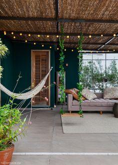 Paredes verdes, teto com cobertura de fibra natural, rede, balanço e espaço de estar.
