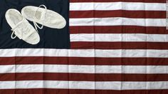"""Images of Hanaa' Malallah's shoes appear in many of her artworks, including being embroidered in """"USA Heritage Flag,"""" from 2012. Malallah is fascinated with the 2008 incident when an Iraqi journalist threw shoes at former President George W. Bush. """"Shoes are our way of resistance,"""" said Malallah."""