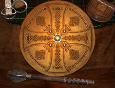 This targe features a cross filled with Celtic knot work. The boss is hand hammered brass. This Scottish Targe was designed by Mike Pruette at CelticLeatherworks.com.