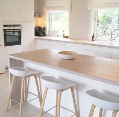 I simply adore this Norwegian home's breakfast bar, modern white kitchen with light wood worktop and flooring and living space. Very Scandi chic with white walls, minimalist style and white stools perfect interior inspiration for kitchen ideas