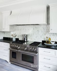 """The custom wood hood and cabinets are painted with Sherwin-Williams' satin oil in """"Crushed Ice."""" Artistic Tile's marble mosaic backsplash sets off a Wolf range. - Photo: Jean Allsopp / Interior & kitchen design: Dana Wolter"""