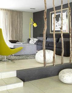 Yellow pops beside the grey tones - bringing in some wood to break up the cool colours and warm up the room,