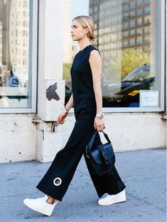 Look de Pernille in an all black jumpsuit and white sneakers with a black handbag.
