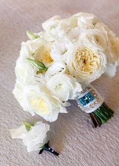 The bride's elegant all-white bouquet features garden roses, ranunculuses and lisianthus.