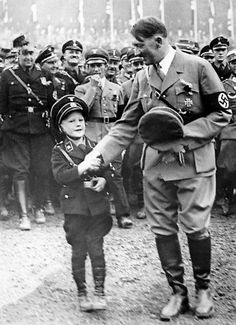 Hitler greeting a little tyke while Goebbels looks like he's licking a recently rolled cigarette (hey, he smoked, anything's possible). Hitler has that little flower sprig in his lapel along with presumably a black carnation. Fuehrer3345 will tell us what that flower is. (via putschgirl)