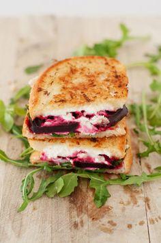 Sanduíche de queijo de cabra com beterraba embebidas em vinho e rucula, com pão francês .