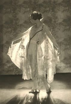Photo by Baron de Meyer, 1919.Helen Lyons, standing slightly turned, lifting her arms and wearing a dress and matching cape by Boue Soeurs, of embroidered batiste, pleated net, baby Irish rose point and Venetian point laces, with ribbon sash and ties. Baron de Meyer