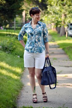 Already Pretty outfit featuring blue floral button-front shirt, white Lee walking shorts, John Fluevog Haight sandals, navy leather bag, sunglasses