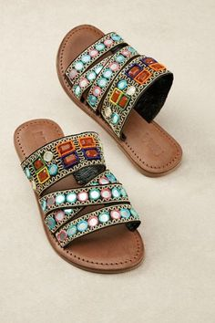 "Tiny mirrors reflect the sunlight and your smart style in these tribal-village inspired sandals, easy slide-ons with colorfully embroidered, beaded and bejeweled fabric straps. Detailed with a -1/4"" heel and man-made sole, they're designed with worldly wanderers in mind. Cassian Sandals - Item #1AN34"