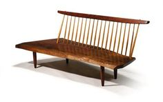 Bench by George Nakashima.    Walnut conoid bench, free edge seat, 21 hickory spindles, cylindrical tapering legs. #FreemansAuction