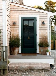 light brown wood house with a black door + white door border | symmetrical plants