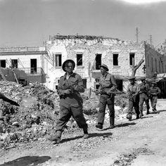 Les troupes britanniques avancent prudemment à travers les ruines de Bizerte au cours de la campagne Tunisie.