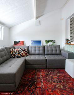 Sotão de casa foi transformado em quarto de tv. Sofá cinza, tapete persa e parede com cobogós.