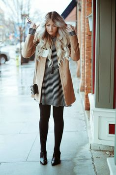 Black and white striped dress. Black tights. Black shoes. Tan coat with white stripe.