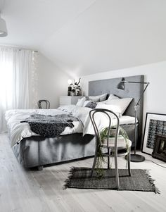 a Scandinavian bedroom with a grey bed, some retro furniture, lamps and lights hanging on the window - DigsDigs Pretty Bedroom, White Bedroom, Dream Bedroom, Modern Bedroom, Monochrome Bedroom, Serene Bedroom, Cosy Bedroom, White Rooms, Bedroom Sets