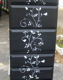 After spraying it with primer and black paint, I felt it needed a little something special, so I stenciled a flowering vine all the way up the front of the drawers.