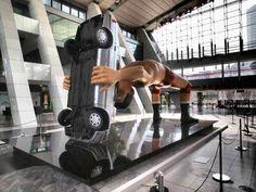 巨大アート:ジャイアント馬場さん、京都市役所前に  2016年10月13日  京都市中京区の市役所前に13日、全長7メートルの故・ジャイアント馬場さんが実物の乗用車に「バックドロップ」を決める巨大アート作品がお目見えした。 モダンな市庁舎とのコントラストが通行人らの注目を集めている。  京都から映画やアートを発信する「京都国際映画祭2016」(13~16日)の一環で、現代美術家の永井英男さん(52)=大阪府泉大津市=の作品を設置した。16日まで設置する。  永井さんは「馬場さんは私にとって強さの象徴。困難に直面した時の人間の強靱(きょうじん)さを表現したかった」という。