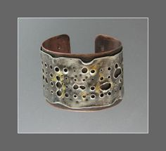 Texture is created by piercing and heating holes until they expand keub boo added for color. Copper back plate offers color contrast and stability. By Connie Fox.